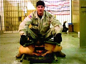 Ivan Frederick - Ivan Frederick, sitting on an Iraqi detainee