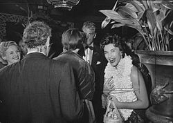Actress Linda Christian wearing a sarong and Hawaiin lei while talking with others at Ciros, 1954.jpg