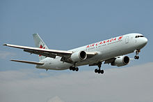 A white 767 with red markings of Air Canada landing with undercarriage extended.