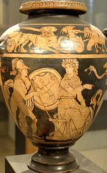 An image painted on the body of a vase. A seated woman speaks to a man behind her while her hand gestures forward. The man wears greaves and a helmet and holds a shield and a spear.