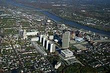Uma vista aérea de Albany mostrando prédios altos no centro, um rio correndo das 11h às 3h da foto, cercado por zonas habitacionais mais verdes