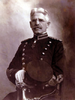 Head and torso of a seated white man with mustache and gray hair wearing a military jacket and white gloves, holding a peaked cap in one hand with the hilt of an ornate sword resting against his leg.