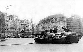 Deux chars d'assaut stationnés sur une place entourée d'immeubles historiques.