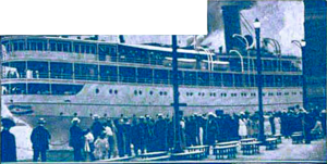 Blue-tinted photograph of a ship, with many people standing in the foreground.