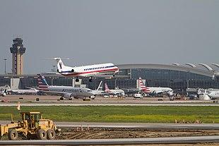 Ein Flugzeug landet, während andere Flugzeuge im Hintergrund geparkt sind