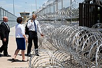 Obama pointing to barbed wire