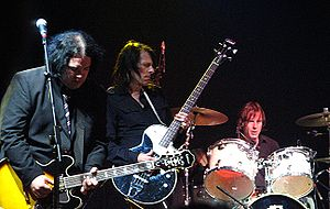 Prominent in the foreground, two guitarists concentrate on their playing, while the drummer, a little behind them to their left, toils away.