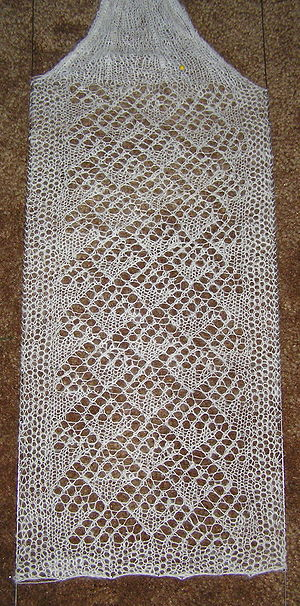 A lace scarf in the process of being blocked.