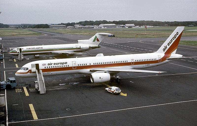 Side view of twin-engine jet on tarmac, with attached airstairs and support vehicle, along with a trijet aircraft in the background.