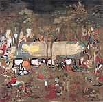 Buddha lying on a platform surrounded by mourners.