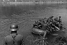 a black and white photograph of a group of German soldiers paddling a rubber boat across a river