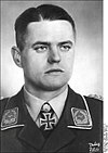 The head and shoulders of a young man, shown from the front. He wears a military uniform, with an Iron Cross displayed at the front of his white shirt collar. His facial expression is a determined and a grim smile; his eyes are looking to the left of the camera.