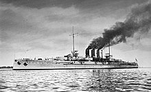 Large gray battleship at sea. Dark smoke streams back from its three closely arranged funnels.