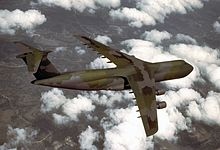 Four-engine jet transport with dark green and gray paint scheme in-flight above clouds.