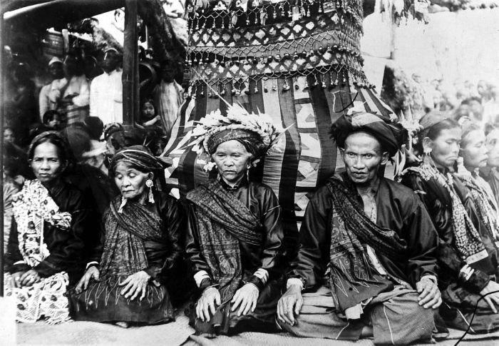 COLLECTIE TROPENMUSEUM Een aantal religieuze specialisten zitten rondom een met textiel bekleed bouwwerk tijdens een oogstfeest te Kumun Sumatra TMnr 10000989