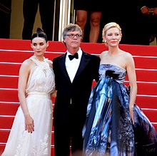 A man wearing a black tuxedo, white shirt, black bow tie, and eyeglasses is standing with his arms around the backs of two women. Behind them are red-carpeted steps. The woman on his right, a brunette, is wearing a haute couture white halter gown with ruffles and embroidery on the skirt; while the woman on his left, a blonde, is wearing a strapless ballgown with prints and shades of blue, light gray, black, and some hints of red.