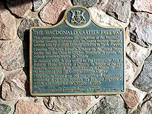 A blue plaque on a stone wall. The plaque has a yellow border, and is mostly rectangular in shape, with the long end oriented horizontally. However, the top side has a camel hump in the centre, with a circle centred at the top of the hump. Inside the circle is an Ontario coat-of-arms. The plaque reads: THE MACDONALD CARTIER FREEWAY This plaque commemorates the completion of the Macdonald-Cartier Freeway (Highway 401), the longest freeway operated without tolls by a single highway authority in North America. Covering 510 miles between Windsor on the Canada–US border and the Ontario-Quebec boundary, it serves the richest economic region in Canada. In January 1965, it was named by The Honourable John Robarts, Premier of Ontario, in honour of the two founding architects of the Confederation of Canada, Sir John A. Macdonald and Sir George-Étienne Cartier. This site is located on the last section of construction, consisting of 15 miles between Ivy Lea and Highway 2, which was completed on October 11, 1968.