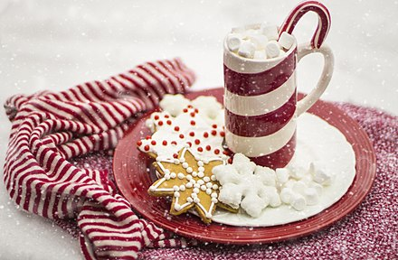 Many traditions enjoy dessert after the main course. Here, a tray of hot chocolate is paired with Christmas-themed ginger bread cookies. Christmas dessert.jpg