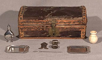 Brit milah - Family circumcision set and trunk, ca. eighteenth century Wooden box covered in cow hide with silver implements: silver trays, clip, pointer, silver flask, spice vessel.