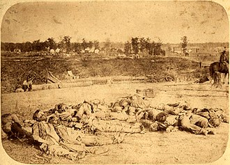 Second Battle of Corinth - Confederate dead lay gathered at the bottom of the parapet of Battery Robinett on October 5. Col. William P. Rogers of the 2nd Texas (left foreground) seized his colors to keep them from falling again and jumped a five-foot ditch, leaving his dying horse and assaulted the ramparts of the battery. When canister shot killed him, he was the fifth bearer of his colors to fall that day.
