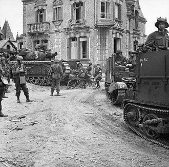 1st Assault Brigade Royal Engineers - Universal carriers with deep wading screens pass through Lion sur Mer. A Churchill AVRE can be seen in the background, 6 June 1944.