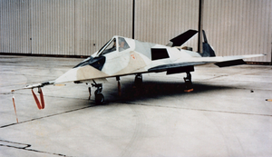 Small jet aircraft with angled surfaces in hangar. It is painted in a disruptive scheme to confused casual onlookers.