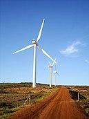 Kırmızı bir toprak yolun yanında rüzgar türbinleri