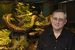 Darrel Frost - Frost next to diorama of a reticulated python.