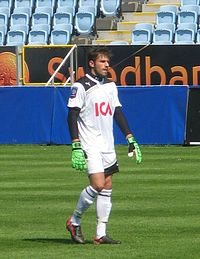 A photograph of a man wearing a white football shirt, green goalkeeper gloves, white shorts and white socks.