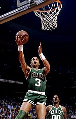 "A man, wearing a green jersey with a word ""CELTICS"" and the number ""3"" written in the front, is jumping while holding a basketball, trying to do a layup."