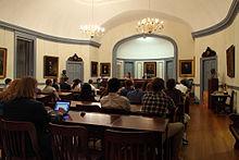 Uma coleção de pessoas sentadas em uma sala branca que tem pinturas em suas paredes.