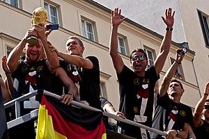 Shkodran Mustafi - Mustafi holding the FIFA World Cup Trophy at Germany's victory parade in Berlin