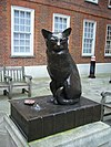 Statue en bronze d'un chat assis sur un livre