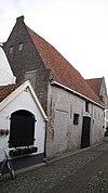 foto van Boerderij met hoog dak, aan de noordzijde afgesloten door een hoge puntgevel met vlechtingen