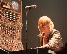 Keith Emerson performs with a complex synthesizer system that is barely visible through a mass of cables that connect its various modules