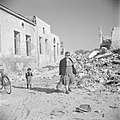 Emigrantenvrouw met kind temidden van door oorlogsgeweld vernielde huizen, Bestanddeelnr 255-1202.jpg