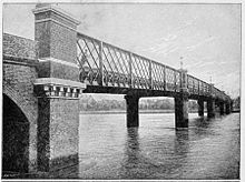 Narrow lattice truss bridge crossing a wide river