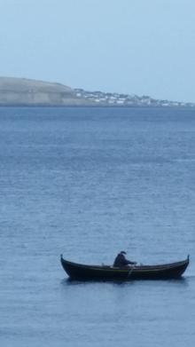 דייג באמצעות סירת משוטים באיי פארו. ברקע המרוחק האי נולסוי