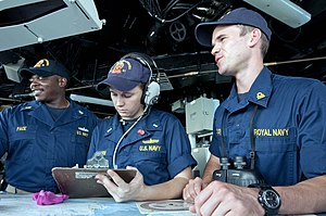 USS Winston S. Churchill - A Royal Navy officer assists on the bridge