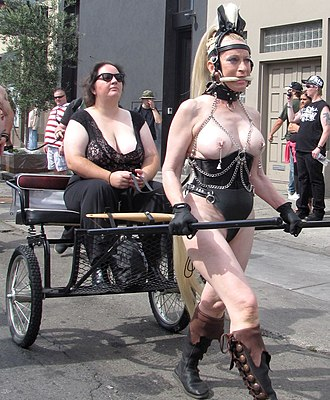 Animal roleplay - A topless pony-girl pulling her mistress seated on a sulky, at USA's Folsom Street Fair, the world's largest leather and kink festival.
