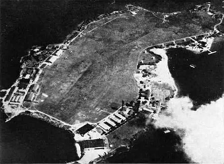 An island nearly three times long as it is wide with buildings scattered around the edges and grassy fields in the center