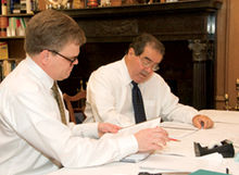 Two men in shirtsleeves work at a table with papers in front of them.
