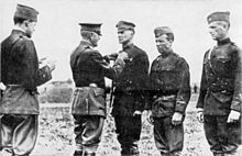 "Three men in uniform are standing side by side. The one on the left is wearing a peaked ""crush cap"" and standing smartly at attention, while the two on the right wear garrison caps and are slouching. A man in a peaked cap and Sam Browne belt is pinning something on the chest of the first man. Behind him stands another man in a garrison cap who is reading a document in his hands."