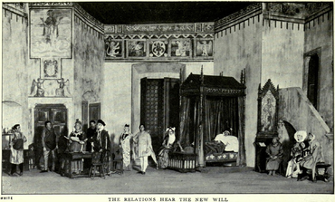 A tall stage set depicting a large room with medieval pictures, patterns and motifs on the upper parts of the walls. On the left, there is an alcove and two sets of doors. At the back is a tall screen and an elaborate curtained four-poster bed containing a man in sleeping garments and a nightcap. To the right is a tall wooden desk with a religious picture in a Gothic frame sideways, near a short staircase leading up to a balcony door. Seven men (two of them tradesmen), three women and a child, all in medieval garments, are standing or sitting around the room listening to an important-looking man who is reading a document out loud.