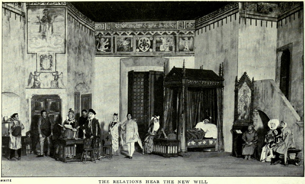 A tall stage-set depicting a large room with medieval pictures, patterns and motifs on the upper parts of the walls. On the left, there is an alcove and two sets of doors. At the back is a tall screen and an elaborate curtained four-poster bed containing a man in sleeping garments and a nightcap. To the right is a tall wooden desk with a religious picture in a gothic frame, sideways-on to a short staircase leading up to a balcony door. Seven men (two of them tradesmen), three women and a child, all in medieval garments, are standing or sitting around the room listening to an important-looking man who is reading a document out loud.