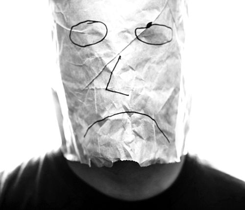 Gray paper bag with sad smiley over head.jpg