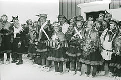 Group of sami in traditional costumes in front of a house.jpg
