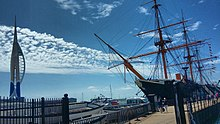 A view of the port side of HMS Warrior alongside Portsmouth Harbour. The Spinnaker Tower can be seen to the far left.