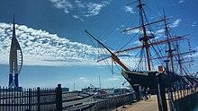 Vido de la babordo de HMS Warrior kune kun Portsmouth Harbour. La Spinakro de Turo povas esti vidita al la malproksima maldekstro.