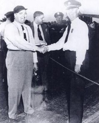 Clive Caldwell - Test Pilot Herbert O. Fisher shakes hands with Curtiss-Wright fire chief; note Caldwell in background, August 1942.